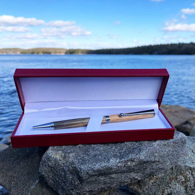 Lobster Trap Wood Pen, made from old, oak lobster traps, that have been retired by Maine lobstermen. It is laying on rocks by the ocean.