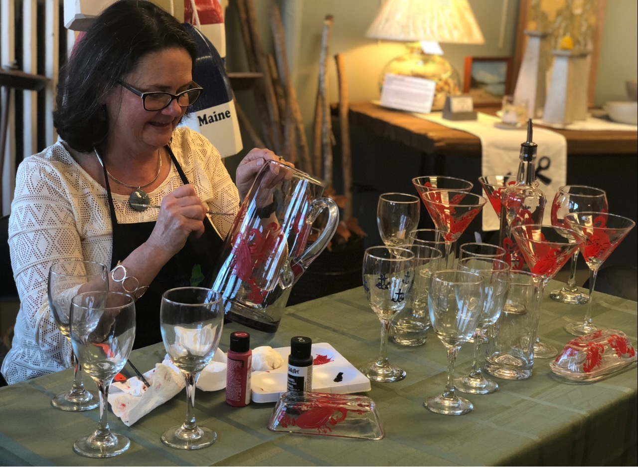 Lisa-Marie hand painting her glassware. She is painting martini glasses, wine glasses and a large glass pitcher.